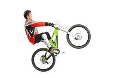 Motorista joven con su salto de la bici de montaña Foto de archivo