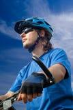 Motorista joven en casco en un fondo del cielo azul Imagen de archivo