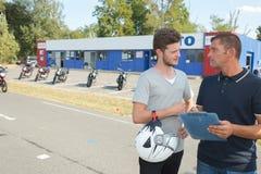 Motorista joven que habla con el curso de aprendizaje de la motocicleta del instructor Fotos de archivo