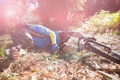 Motorista masculino de la montaña caido de su bicicleta en bosque Foto de archivo libre de regalías