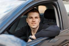 Motorista masculino novo considerável em um carro preto imagem de stock