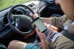 Motorista masculino que olha o mapa no smartphone Fotos de Stock Royalty Free