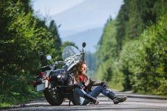 Motorista masculino que se sienta en el camino cerca de la motocicleta Fotos de archivo libres de regalías