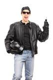 Motorista masculino que sostiene llave y un casco Imágenes de archivo libres de regalías
