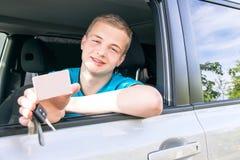 Motorista Menino adolescente caucasiano que mostra um cartão branco vazio, carro Fotografia de Stock