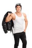 Motorista muscular que sostiene una chaqueta de cuero Fotografía de archivo libre de regalías