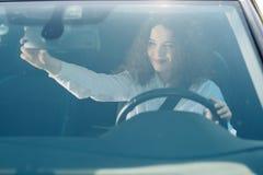 Motorista no espelho retrovisor Jovem mulher atrativa no desgaste do negócio que olha no espelho retrovisor e que sorri ao conduz imagens de stock