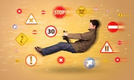 Motorista novo com sinais de estrada em torno dele Imagem de Stock