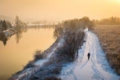 Motorista que completa un ciclo en la trayectoria junto a un río Foto de archivo