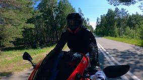 Motorista que conduce rápidamente en un camino, casco que lleva almacen de video