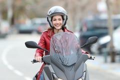 Motorista que conduce una moto en la calle Fotos de archivo libres de regalías
