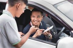 Motorista que mostra seu telefone celular a um homem que está ao lado de seu Ca imagem de stock