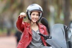 Motorista que muestra llaves de la moto en su vespa Foto de archivo libre de regalías