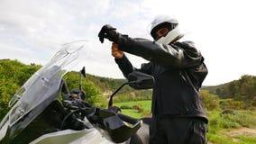 Motorista que prepara su moto de los deportes para un entrenamiento del camino almacen de video