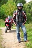 Motorista que se coloca en la carretera nacional cerca de la bici Imagenes de archivo