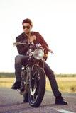 Motorista que se sienta en la motocicleta de la aduana del vintage Retrato al aire libre de la forma de vida Imágenes de archivo libres de regalías