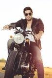 Motorista que se sienta en la motocicleta de la aduana del vintage Retrato al aire libre de la forma de vida Fotos de archivo libres de regalías