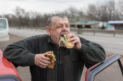 Motorista superior caucasiano que devora o no espeto do lyulya no lavash perto de seu carro imagens de stock