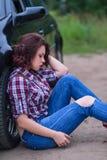 Motorista triste da mulher que senta-se perto de seu carro quebrado foto de stock royalty free
