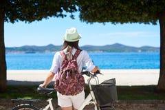 Motorista turístico de la mujer joven con la bicicleta de la ciudad en la ciudad cerca del mar imagenes de archivo