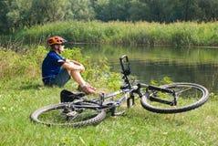 Motorista y bicicleta jovenes Fotos de archivo libres de regalías