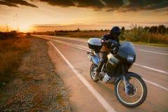 Motorista y motocicleta en el camino en la puesta del sol Imagenes de archivo