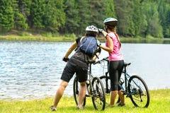 Motoristas jovenes en el lago que miran el bosque Imagen de archivo