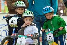 Motoristas jovenes en la competición de la bicicleta del niño. Foto de archivo libre de regalías
