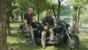 Motoristas masculinos brutales que charlan sobre la moto al aire libre almacen de video