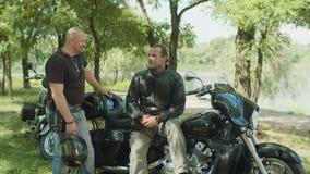 Motoristas masculinos positivos que charlan cerca de la moto almacen de video