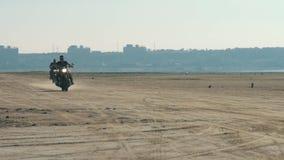 Motoristas que montan a lo largo de la playa arenosa Motocicleta del paseo de dos motoristas en desierto metrajes