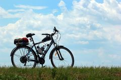 Motorized bicycle on green grass against blue sky. Background Royalty Free Stock Photos