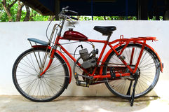Motorized bicycle. Red Motorized bicycle The retro royalty free stock images