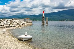Motorized boat moored at shore with ship channel light behind. Motorized boat moored at stone shore with ship channel light behind royalty free stock photos