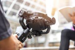 Motorized gimbal, videographer using dslr camera anti shake tool royalty free stock photos