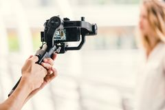 Motorized gimbal, videographer using dslr camera anti shake tool for stabilizer. Record video scene stock photo