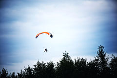 Motorized hang glider on the blue sky. Stock Image