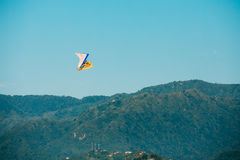 Motorized Hang Glider Flying Over Mountain Hills In Blue Clear Sunny Sky Royalty Free Stock Image