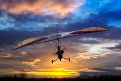Motorized hang glider flying. In the sunset Stock Photo