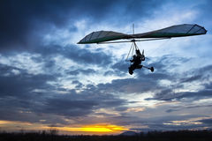 Motorized hang glider flying. In the sunset Royalty Free Stock Photography