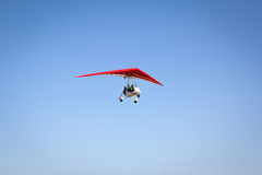 Motorized hang glider soaring in the blue sky Royalty Free Stock Photo