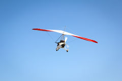 Motorized hang glider soaring in the blue sky Stock Photos