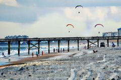 The motorized kites fly over the ocean pier as a group. The motorized kites are impressive enough as one, but even more so with three flying side by side royalty free stock photo
