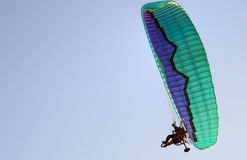 Motorized paraglider. Person flying in a motorized green and blue paraglider royalty free stock photos