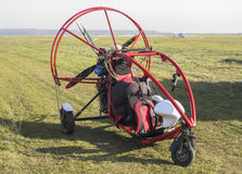 Motorized paraglider on airfield. Stationary motorized paraglider on airfield and lightweight plane in the background stock images