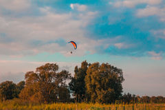 Motorized paraglider flying in rural area during sunset Stock Photography