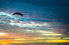 Motorized paraglider flying up high on the sky. By the sunset Royalty Free Stock Photography