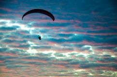 Motorized paraglider flying up high on the sky. By the sunset Stock Photo