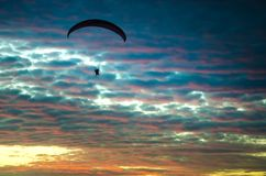 Motorized paraglider flying up high on the sky. By the sunset Royalty Free Stock Photos