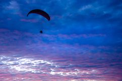 Motorized paraglider flying up high on the sky. By the sunset Royalty Free Stock Image